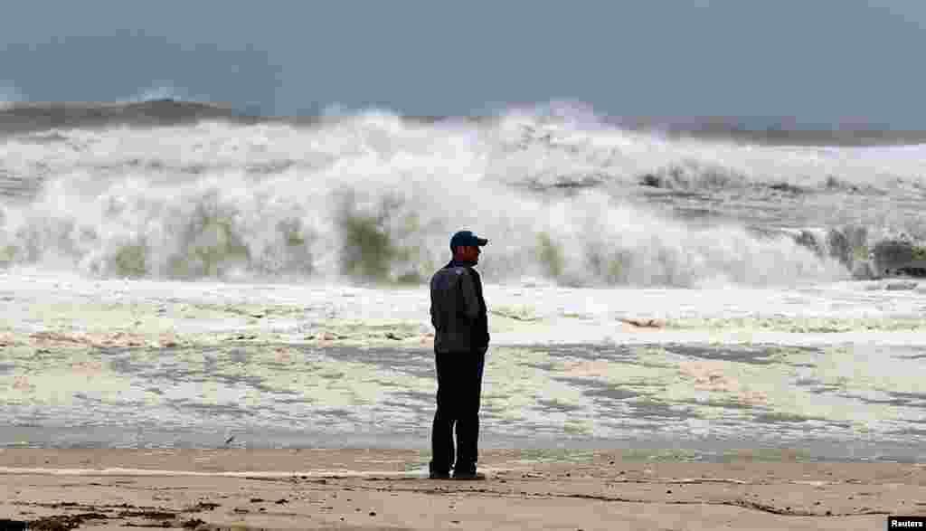 Un hombre observa las olas en la playa de Southampton, cercana a Nueva York.