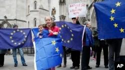 Pendukung keanggotaan Uni Eropa berunjuk rasa sambil membawa bendera Uni Eropa pada hari pertama sidang yang membahas apakah pemerintah Perdana Menteri Theresa May dapat memicu keluar Inggris dari Uni Eropa tanpa tindakan Parlemen, di Pengadilan Tinggi, London, 13 Oktober 2016 (AP Photo/Alastair Grant).