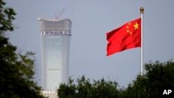 A Chinese national flag at Tiananmen Square flutters against the capital city tallest skyscraper China Zun Tower under construction at the Central Business District in Beijing Thursday, June 14, 2018.
