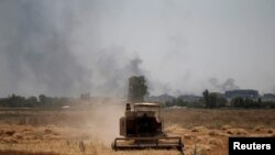FILE - Smoke billows from the positions of the Islamic State militants as a harvester gathers the wheat crop from a field in western Mosul, Iraq, June 19, 2017.