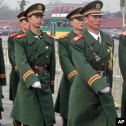 天安门广场上警察列队行进。学者认为北京为保政权采取动之以利和压之以力这两手