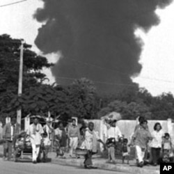 Fleeing Phnom Penh residents carry their belongings along Pochentong airport road after a fuel dump exploded on Sunday July 6, 1997. Fear spread through the city as scattered fighting broke out throughout the capital. Armed forces sealed off Cambodia s wa
