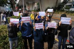 Sejumlah aktivis pro-demokrasi menunjukkan poster di luar Pengadilan West Kowloon setelah Joshua Wong, Agnes Chow, dan Ivan Lam divonis hukuman penjara, Rabu, 2 Desember 2020. (Foto: Tommy Walker/VOA)