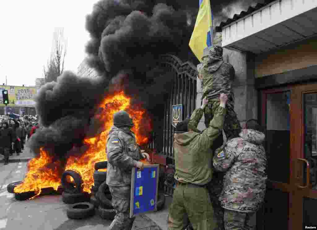 """""""Aydar"""" batalyonunun döyüşçüsü batalyonun dağıdılması tələbi ilə Kiyevdə keçirilən aksiya zamanı Müdafiə Nazirliyinin binasından Ukrayna bayrağını çıxarır - Kiyev, 2 fevral, 2015"""