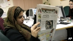 FILE - Iranian journalist Elahe Khosravi, reads Iranian daily newspaper Hamshahri, in Tehran, Iran on Tuesday, Feb. 7, 2006. The prominent Iranian newspaper said it would hold a competition for cartoons on the Holocaust to test whether the West extends the principle of freedom of expression to the Nazi genocide as it did to the caricatures of the Prophet Muhammad.