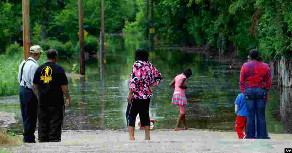 Местные жители наблюдают за поднимающемся уровнем воды в городе Виксбург, штат Миссисипи