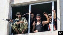 FILE - Free Syrian Army fighters give the victory sign, in Jarablus, Syria. Veteran Syrian rebels who have fought Assad for years are struggling to find a place in a bewildering battlefield where several wars are all being waged at once by international powers, Aug. 31, 2016.