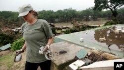 26일 텍사스 윔벌리 마을이 홍수로 범람한 가운데 한 여성이 무너진 건물 잔해 속에서 물건을 건지고 있다.