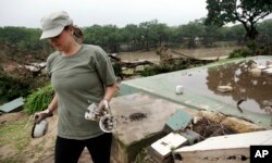 Amanda Calaway pulls unbroken cups and bowls from the debris where a cabin was stripped from its foundation behind her in flood waters from the Blanco River days earlier, May 26, 2015, in Wimberley, Texas.