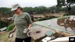 Amanda Kalavej izvlači nepolomljene čaše i činije iz ostataka kolibe koju je iz temelja iščupala nabujala voda reke Blanko.