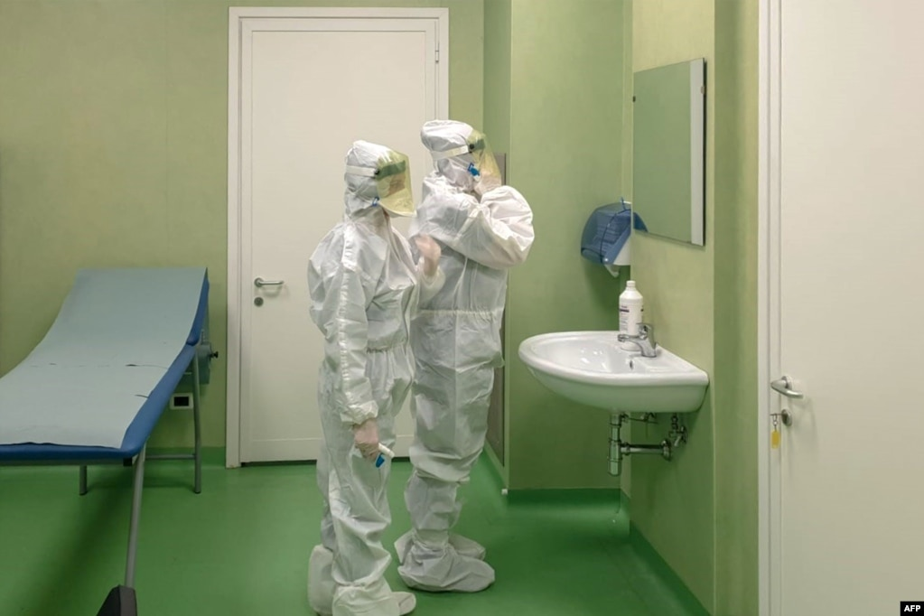 Members of a health team get ready to carry out health measures and procedures against a new coronavirus, after people land at Rome's Fiumicino airport on a flight from Wuhan, China.
