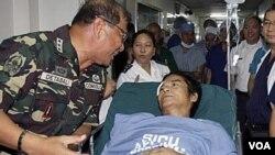 Komandan militer Filipina Roland Detabali berbicara dengan seorang pemberontak, Tirso Alcantara yang dirawat di Manila.