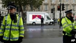"""伦敦街头一辆面包车上写着""""西藏一定会自由""""的口号从习近平的支持者前经过(2015年10月21日)"""