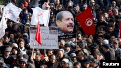 Tunisians hold a placard with an image of the late secular opposition leader Chokri Belaid during his funeral procession in the Jebel Jelloud district in Tunis, February 8, 2013.