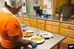 Jon Morales, left, chef at the Haven apartments, prepares dinner featuring bake talapia for residents at three dollars a plate, Dec. 8, 2015, Bronx, N.Y.