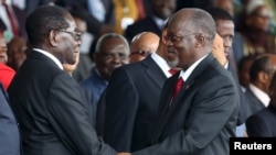 Tanzania's President-elect John Magufuli (R) meets Zimbabwe's President Robert Mugabe before his inauguration ceremony at the Uhuru Stadium in Dar es Salaam, November 5, 2015. REUTERS/Emmanuel Herman - RTX1UW3F