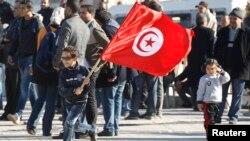 Un Tunisien marchent lors d'un rassemblement un an après la fin de la dictature à Tunis, Tunisie, le 17 décembre 2013.