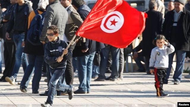A Tunisian boy waves a flag as he runs during a rally to mark the third anniversary of the Tunisian revolution, in Tunis, Tunisia, Dec. 17, 2013.