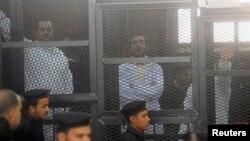 Nhà hoạt động Ahmed Maher (phải), Ahmed Douma (giữa) và Mohamed Adel, những người sáng lập phong trào 6 tháng Tư, đằng sau song chắn tại tòa án Abdeen ở Cairo, 22/12/2013.