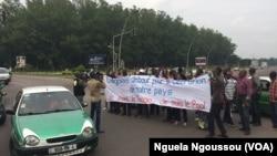 Quelques jeunes brandissent un calicot lors d'une marche de l'opposition à Brazzaville, Congo, 8 juin 2017. (VOA/Ngouela Ngoussou)