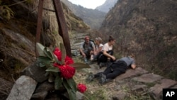 FILE - In this March 27, 2017 photo, Elizabeth Brenner, third right, and her family sit at the spot on the Milam Glacier Trail where Brenner's son, Thomas Plotkin, slipped and fell more than 300 feet down a steep gorge and into the raging Goriganga river in 2011.