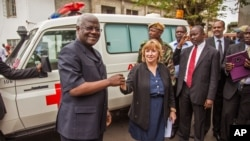FILE - Sierra Leone President Ernest Bai Koroma, left, is handed the keys to an ambulance by U.S. Embassy representative Kathleen FitzGibbon, center, one of five ambulances donated by the U.S. to help combat the Ebola virus in Freetown, Sierra Leone.