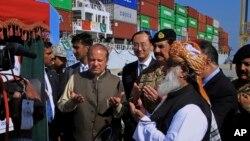 Perdana Menteri Pakistan Nawaz Sharif (tengah) dan Komandan Angkatan Darat Jenderal Raheel Sharif (keempat dari kanan), berdoa setelah meresmikan rute baru perdagangan internasional di pelabuhan Gwadar, 700 kilometer dari Karachi (13/11). (AP/Muhammad Yousuf)