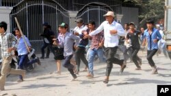 Cambodian garment workers run as they escape for safety in front of a factory of Yak Jin in Kambol village on the outskirts of Phnom Penh, Cambodia, Thursday, Jan. 2, 2014.