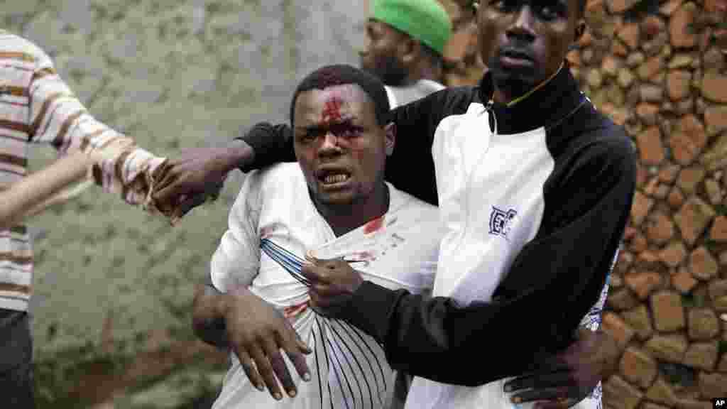 Jean Claude Niyonzima, un membre présumé d'Imbonerakure la milice de la jeunesse du parti au pouvoir, pris par une foule qui se rassemble autour de sa maison, alors que les manifestations se poursuivent contre la décision du président Pierre Nkurunziza de briguer un troisième mandat dans le quartier de Cibitoke de Bujumbura, au Burundi, jeudi 7 mai 2015.