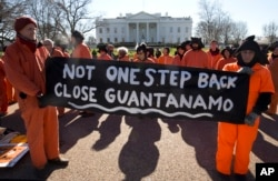 """Protesters wearing orange jumpsuits depicting Guantanamo Bay detainees, hold a sign that reads """"Not One Step Back Close Guantanamo"""" participate in a rally outside of the White House in Washington Monday, Jan. 11, 2016, calling for a close of the detention center at the U.S. base at Guantanamo Bay, Cuba."""