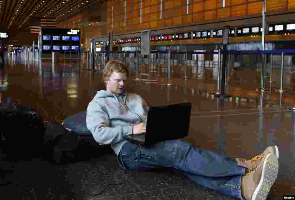 Rasmus Thomsen of Denmark works on his computer as he waits at Boston Logan International Airport after flights were cancelled or delayed due to a massive winter storm, in Boston, Massachusetts Feb. 8, 2013.