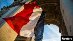 file - The French flag flies under the Arc de Triomphe.