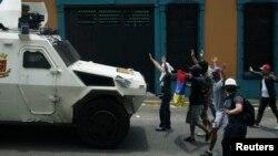 Manifestantes antigubernamentales se plantan frente a un vehículo de la Guardia Nacional durante una protesta en San Cristóbal.