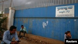 FILE - People wait for garment workers to leave a factory in a suburb of Phnom Penh.