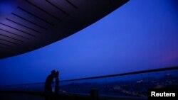 马来西亚伊斯兰当局的一名神职人员在吉隆坡郊外用望远镜观看新月。
