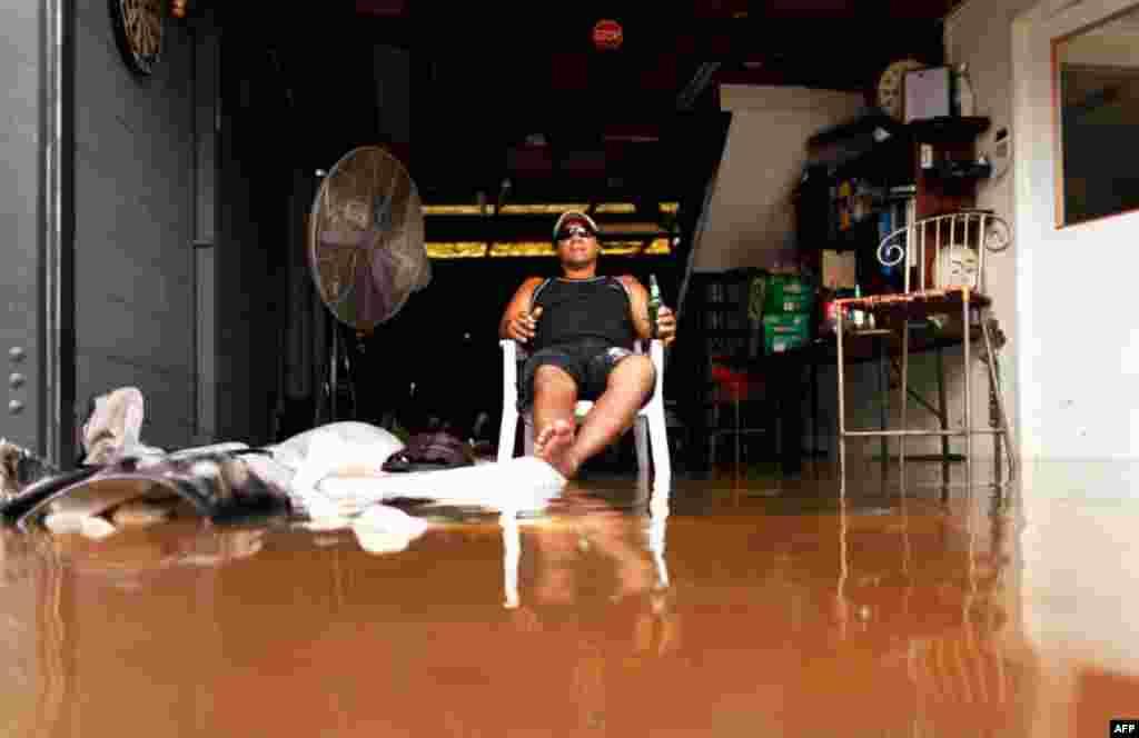 13 Ocak: Brisbane'de su basan otomobil tamirhanesinde oturup bezgin bir halde birasını yudumlayan Avustralyalı. Tarihinin en büyük sel felaketine maruz kalan Avustralya'nın üçüncü büyük kenti Brisbane de sular altında. En kötüsü açıkta oluşan yeni bir kas
