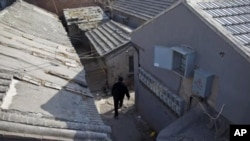 A man walks through the narrow alleys of a hutong in Beijing.