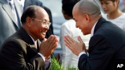 Cambodia's King Norodom Sihamoni, right, greets Heng Samrin, left, National Assembly President, before an annual royal plowing ceremony in Phnom Penh, Cambodia, file photo.