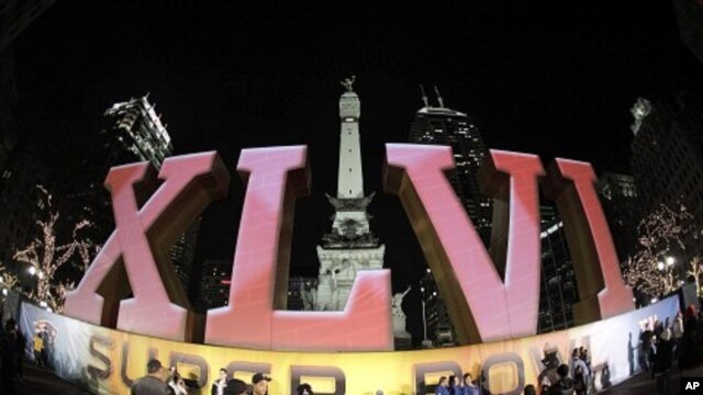 In this photo taken with a fisheye lens, football fans pose for photos in front of the Super Bowl XLVI logo on Monument Circle in Indianapolis, February 1, 2012.