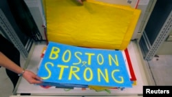 Archivist Marta Crilly holds a poster, an artifact saved from the makeshift Boston Marathon bombing memorial, at the City Archives in Boston, Massachusetts, March 27, 2014.
