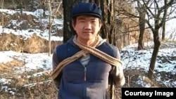 张盼成在甘肃老家村庄把自己绑在树上拍照(华涌推特照片)