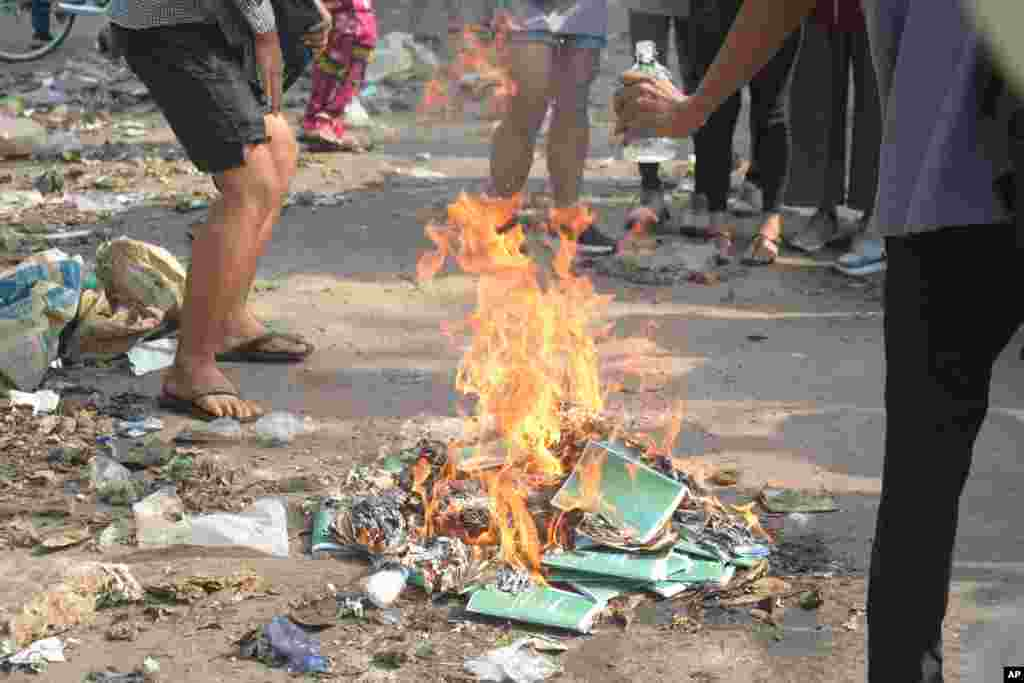 Anti-coup protesters burn constitution books at Tarmwe township in Yangon, Myanmar. Opponents of military government declared the country's 2008 constitution void and put forward an interim replacement charter in a major political challenge to the ruling junta.