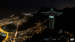 FILE - The Portuguese word 'Hunger' is projected over the Rio's Christ the Redeemer statue amid the new coronavirus outbreak in Rio de Janeiro, Brazil, May 10, 2020.