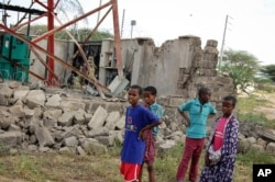 Children look at a damaged telecommunications mast after an attack by al-Shabab extremists in the settlement of Kamuthe in Garissa county, Kenya, Jan. 13, 2020.