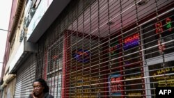 A woman outside a closed nail parlour and spa salon in downtown Atlanta, Georgia, on April 23, 2020, where the governor takes a massive gamble by allowing businesses like gyms and hair salons to re-open