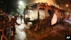 آتش نشانان اتوبوسی را که در جریان تظاهرات به آتش کشیده شده است، خاموش میکنند.