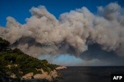 Tiga pesawat pemadam kebakaran terbang melewati kepulan asap, saat kebakaran hutan di La Couronne, dekat Marseille, Perancis, 4 Agustus 2020. (Foto: dok).