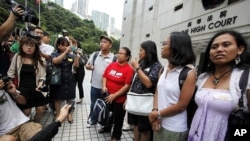 Eman Villanueva (L), vice chairperson of the Filipino Migrant Workers Union, and Dolores Balladares (2nd L), chairperson of United Filipinos in Hong Kong, along with other representatives, meet journalists outside the High Court in Hong Kong August 22, 20
