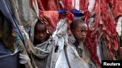 Pengungsi anak memperlihatkan wajah mereka diantara robekan kain yang menjadi tenda mereka di kompleks penampungan Sayyidka Howlwadag, Mogadishu, 19/8/2013.