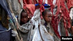 Displaced children peer through holes in the fabric used to make their temporary tent at Sayyidka camp in the Howlwadag district, south of Mogadishu, August 19, 2013.